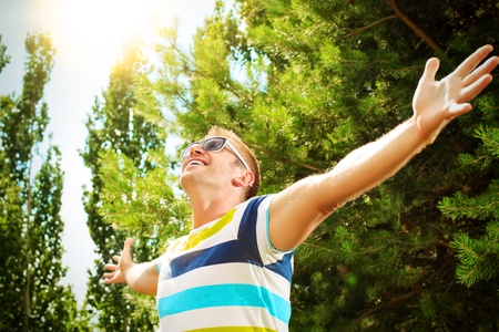 Happy mature man stands outdoor and spread his arms with joy. photo
