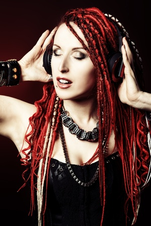 Expressive girl in headphones with great red dreadlocks. photo