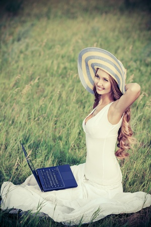 Beautiful smiling young woman sitting with a laptop outdoors. photo