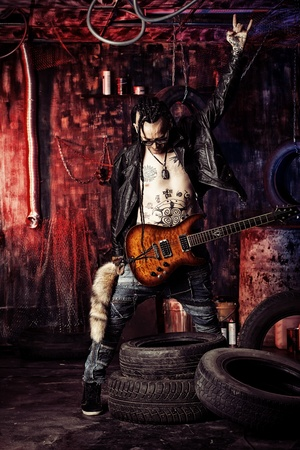 harmonist: Heavy metal musician is playing electrical guitar in the old garage.