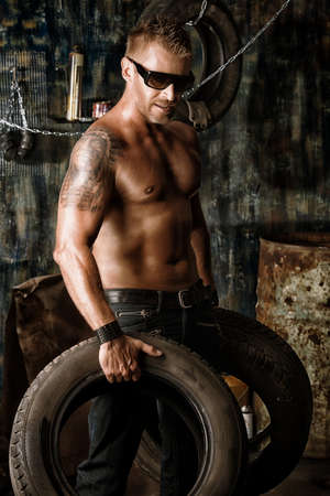 Handsome muscular man in the old garage. photo