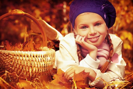 Portrait of a cute girl with a basket full of leaves posing at the autumn park  photo