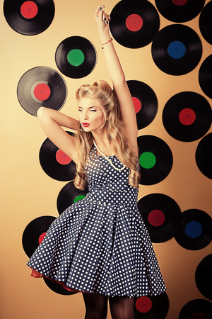 Charming pin-up woman with retro hairstyle and make-up posing with vinyl record. photo