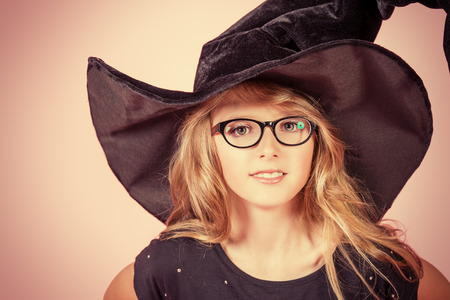 halloween costume: Pretty ten years girl in a witch costume smiling at camera. Pink background. Halloween.