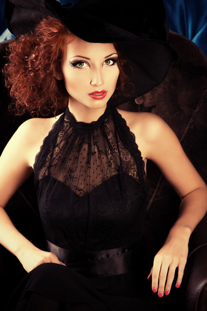 Portrait of an enchanting witch woman, beautiful and glamorous. Halloween.  photo