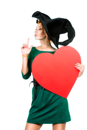 Charming red-haired witch holding red heart. Halloween. Isolated over white.  photo