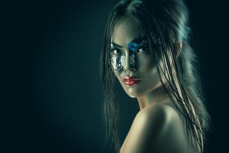 fantasy makeup: Portrait of an asian model with fantasy make-up. Black background.