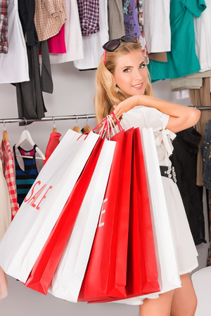 Fashionable lady standing with a lot of shopping bags in a store. photo