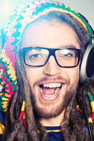 Portrait of a happy rastafarian young man listening to music in headphones. photo