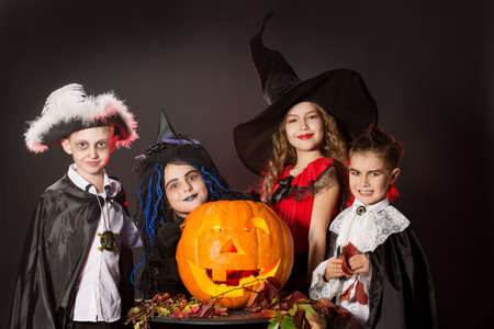 imp: Cheerful children in halloween costumes posing with pumpkin. Over dark background. Stock Photo