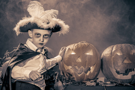 Little boy in halloween costume of pirate posing with pumpkins. Black-and-white. photo