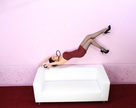 flying woman: Charming fashionable woman flying over sofa in a pink room.