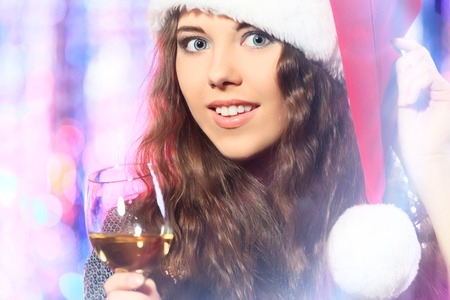 Pretty girl in Christmas clothes on a party. Disco lights in the background. photo