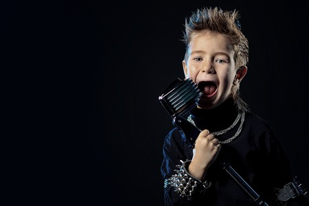 hardrock: Emotional little boy is singing into a microphone like a rock musician.  Stock Photo