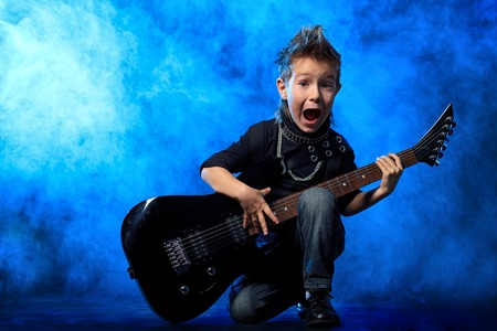 hardrock: Cool little boy posing with electric guitar like a rock singer. Stock Photo