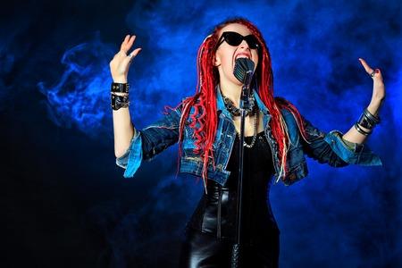 modern rock: Modern rock singer singing into a microphone. Stock Photo