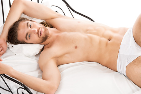 Handsome man lying in a bed. Isolated over white. photo