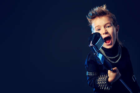 pop star: Emotional little boy is singing into a microphone like a rock musician.  Stock Photo