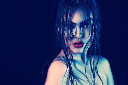 caritas pintadas: Retrato de un modelo asiático con maquillaje de fantasía. Fondo negro.