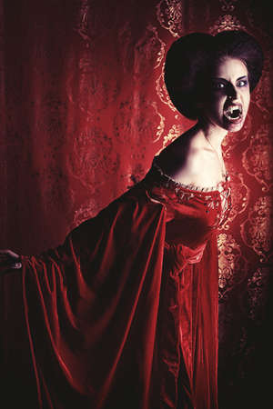 female vampire: Portrait of a bloodthirsty female vampire over red vintage background.
