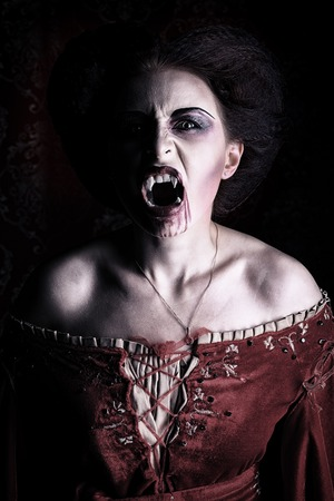 bloodthirsty: Close-up portrait of a bloodthirsty female vampire. Stock Photo