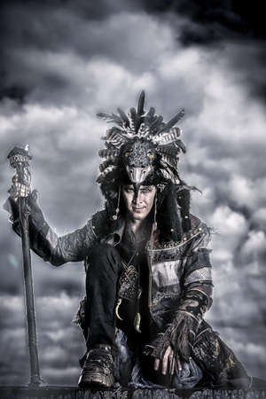 warrior tribal: Portrait of a shaman dancing over cloudy sky.