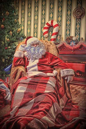 Santa Claus having a rest in a comfortable chair near the fireplace at home.  Stock Photo - 22450064