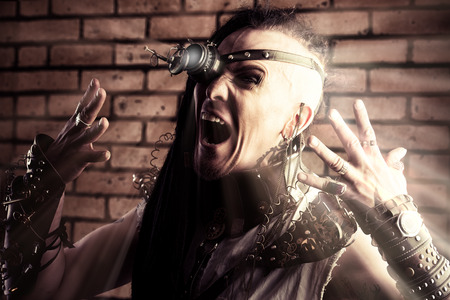Portrait of a steampunk man with a mechanical devices over brick wall. Stock Photo - 22450073