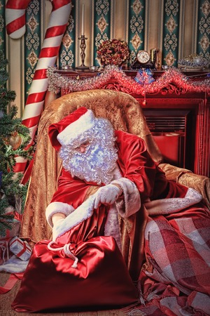Santa Claus having a rest in a comfortable chair near the fireplace at home. Stock Photo - 22450075