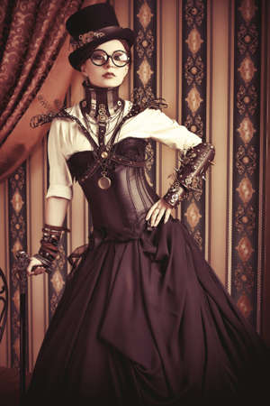 Full length portrait of a beautiful steampunk woman over vintage background. photo