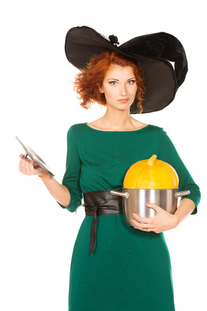 arcanum: Charming red-haired witch holding a pan with pumpkin. Halloween. Isolated over white.