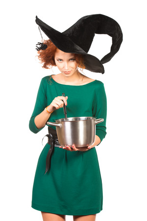 arcanum: Charming red-haired witch brews a witchs brew. Halloween. Isolated over white.