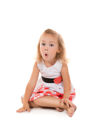 petite fille avec robe: Petite fille mignonne en robe blanche assis sur un plancher. Isolé sur blanc. Banque d'images
