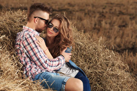 haystack: Romantic young couple in casual clothes sitting together in haystack.