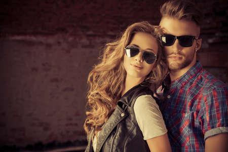 homem: Casal de jovens em roupas jeans posando ao ar livre sobre a parede de tijolos. Imagens
