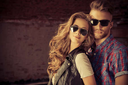 sonnenbrille: Paare der jungen Leute in Jeans-Kleidung posiert im Freien über Mauer. Lizenzfreie Bilder