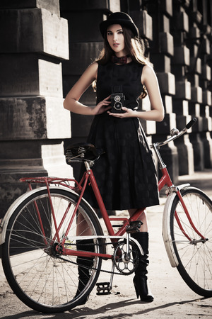 Beautiful brunette standing near her old bicycle and holding the old camera over city background. Retro style. photo