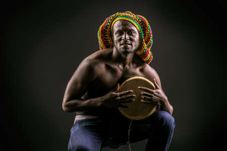 Rastafarian african american man playing his drum. Over dark background. photo