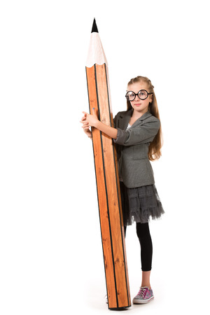 Full length portrait of a cute ten years girl in spectacles holding a huge pencil. Education. Isolated over white. photo