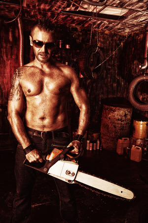 handsome old man: Expressive handsome muscular man with a chainsaw in the old garage.