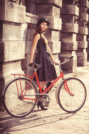 Beautiful brunette standing near her old bicycle over city background. Retro style. photo
