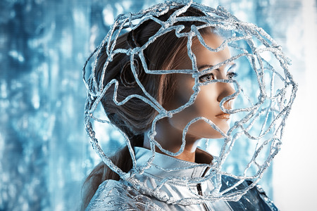 robot woman: Beautiful young woman in silver latex costume with futuristic hairstyle and make-up. Sci-fi style.