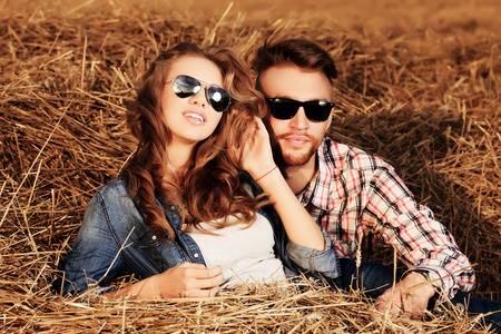 Romantic young couple in casual clothes sitting together in haystack. photo