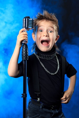 Emotional little boy is singing into a microphone like a rock musician.  photo