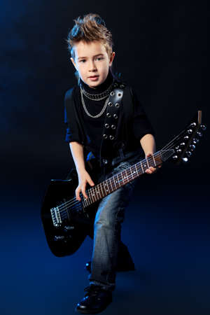 Cool little boy posing with electric guitar like a rock singer. photo