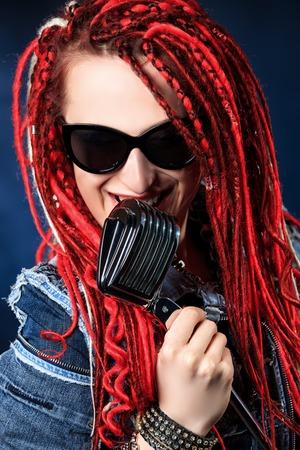 modern rock: Portrait of a modern rock singer singing into a microphone.