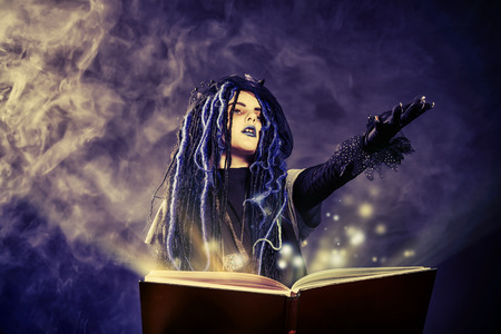 spell: Little girl in a costume of witch casts a spell over magic book over dark . Stock Photo