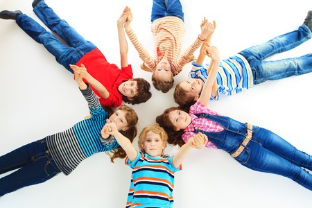 Group of cheerful children lying on a floor together  Isolated over white  photo