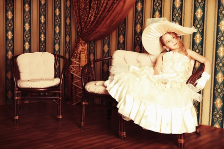 Portrait of a charming little lady in a beautiful elegant dress posing in a vintage interior.  photo