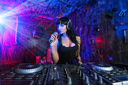 Beautiful sexual DJ girl working on a party in the old garage. Stock Photo - 22710697
